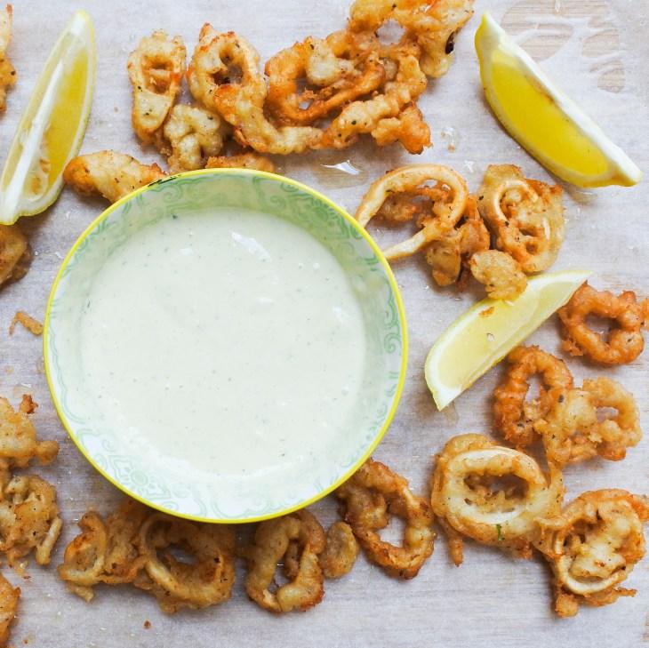 Golden fried calamari with lemon wedges and a creamy aioli