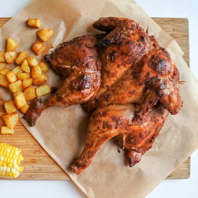 spatchcock chicken on cutting board with fried potatoes