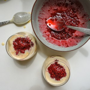 Two cranachan parfaits with bowl of raspberry sauce