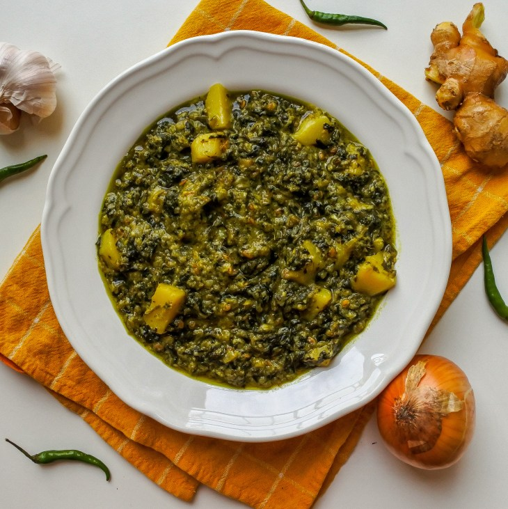 A bowl of Aloo Palak next to ginger, garlic, onion and chiles