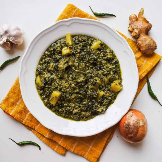Spinach and potato curry in a bowl next to garlic, ginger, chiles and onion