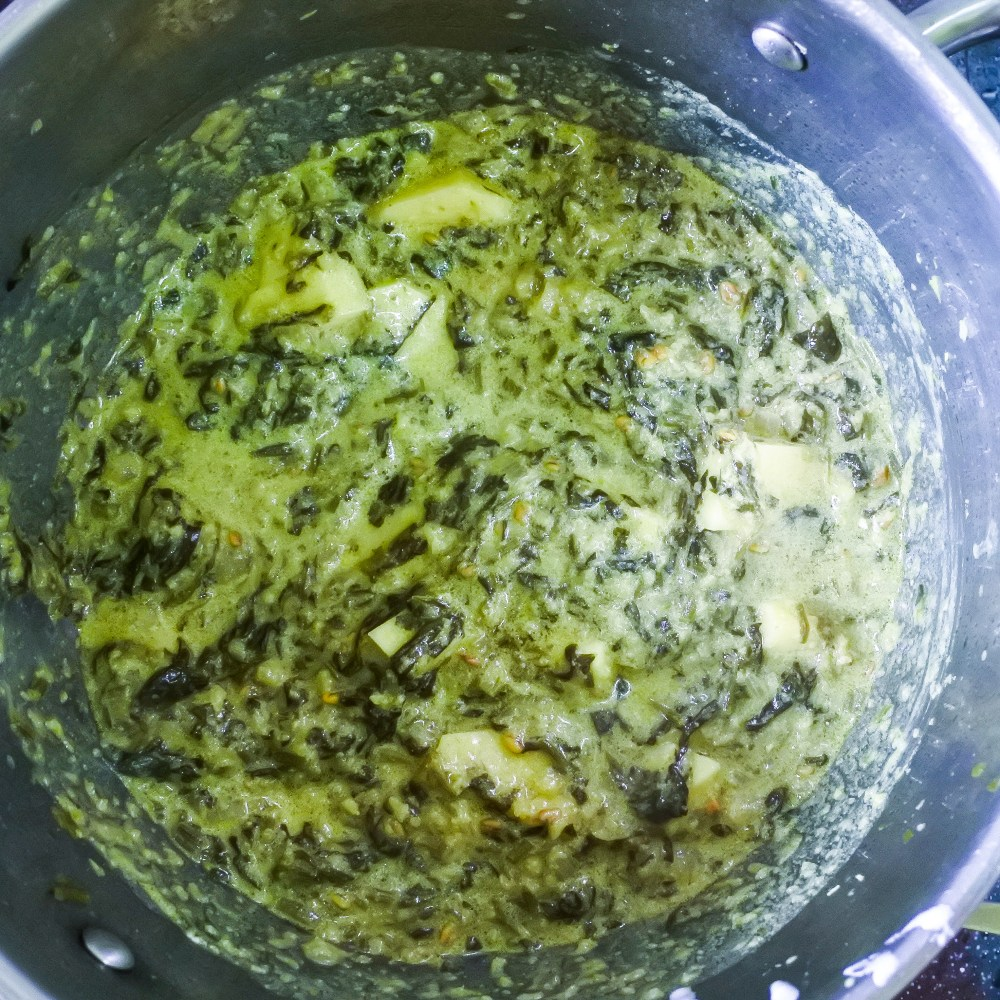 Spinach and potato curry in a large cooking pot