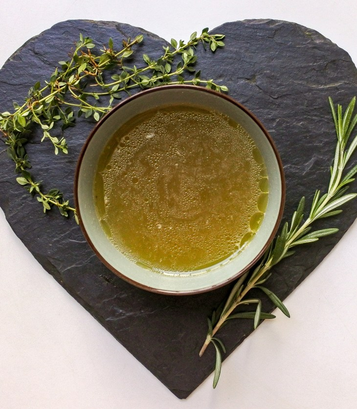 a bowl of chicken broth next to sprigs of fresh thyme and rosemary
