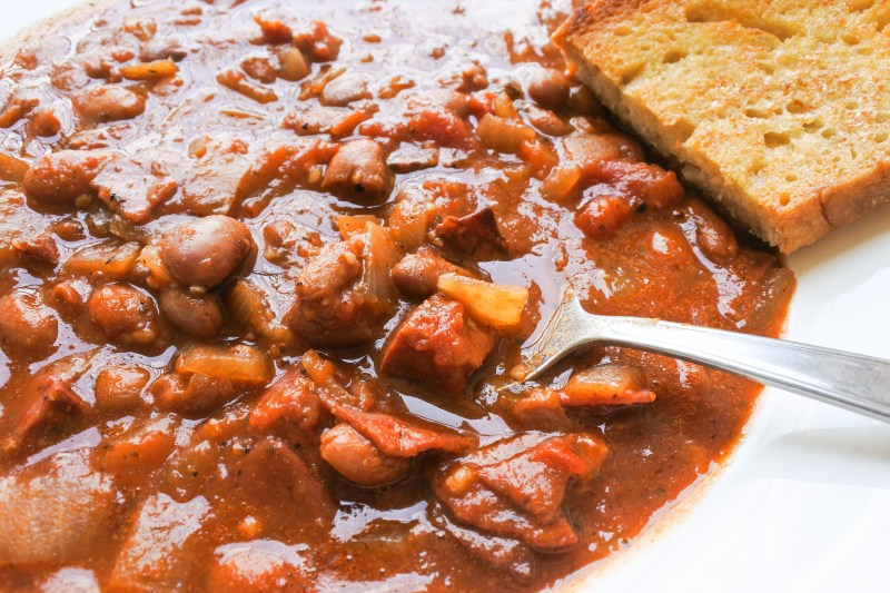 spoon in chorizo bean stew with toasted bread