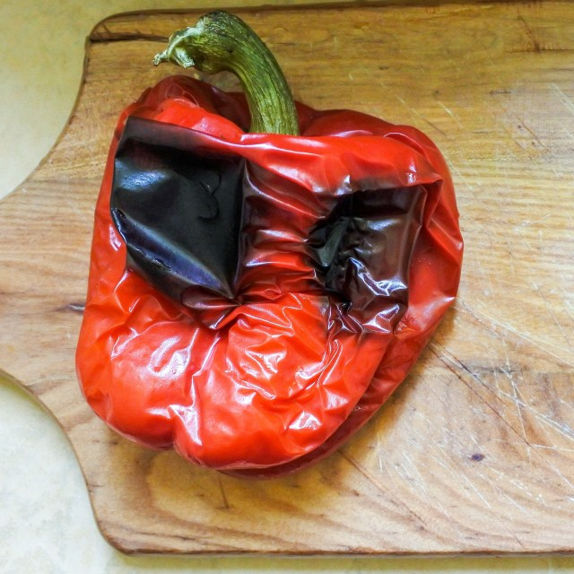whole roasted red pepper on a cutting board