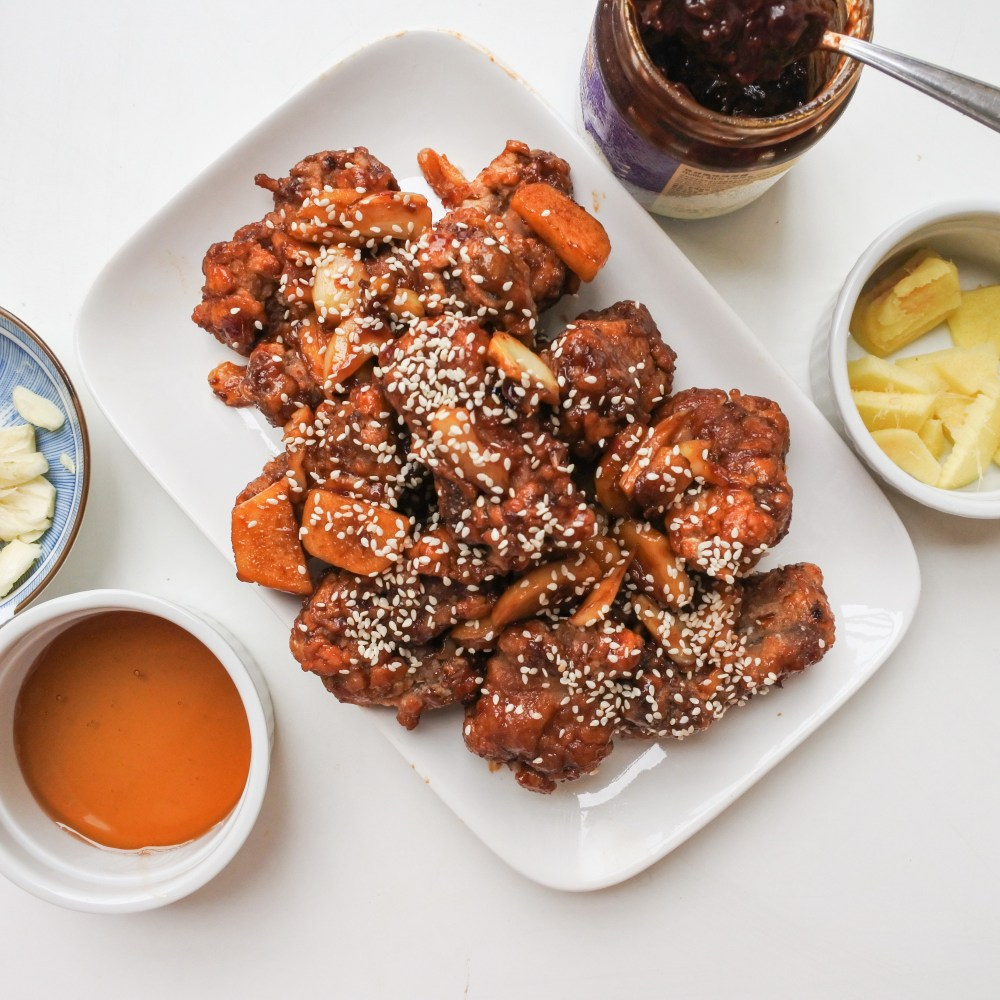 Asian style pork ribs covered in honey garlic sauce on a plate next to bowls of Guilin chili paste, honey, garlic and ginger