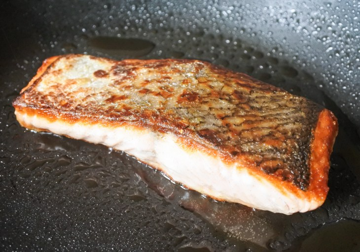a salmon fillet frying in a pan