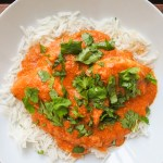 Chicken Tikka Masala over Basmati rice in a bowl garnished with chopped cilantro