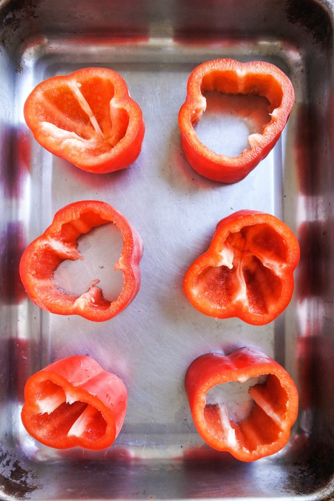 red bell peppers cut in half and in a baking tray