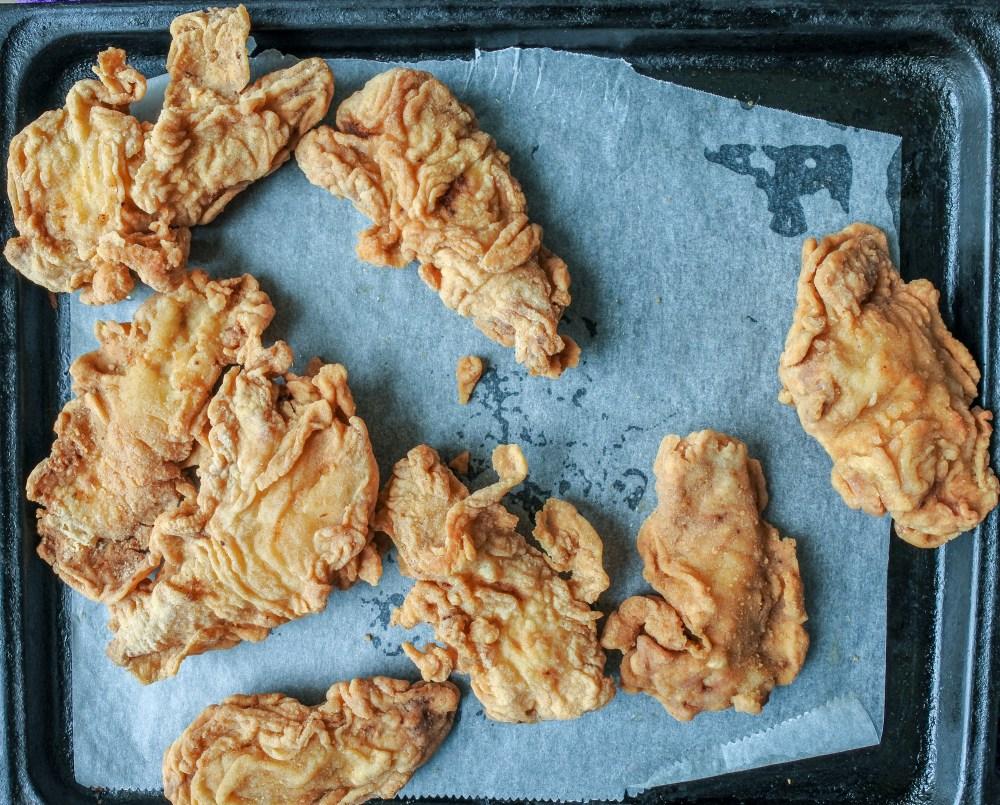 Crispy chicken tenders rewarmed on a baking tray