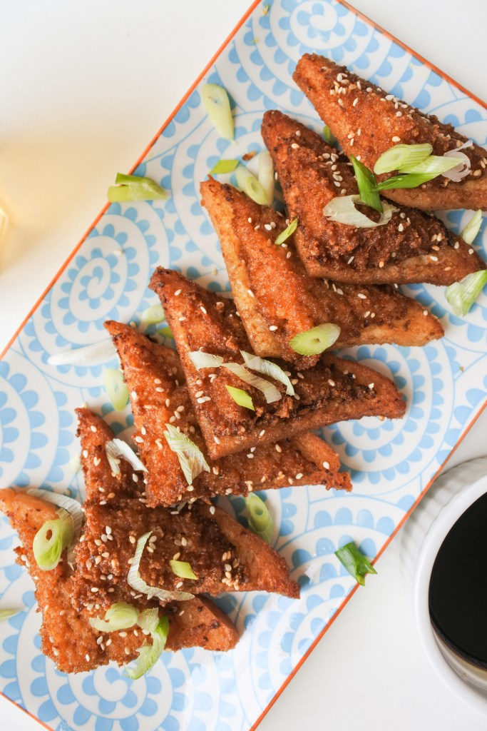 shrimp/ prawn toast lined up on a serving tray with black vinegar and chopped scallions
