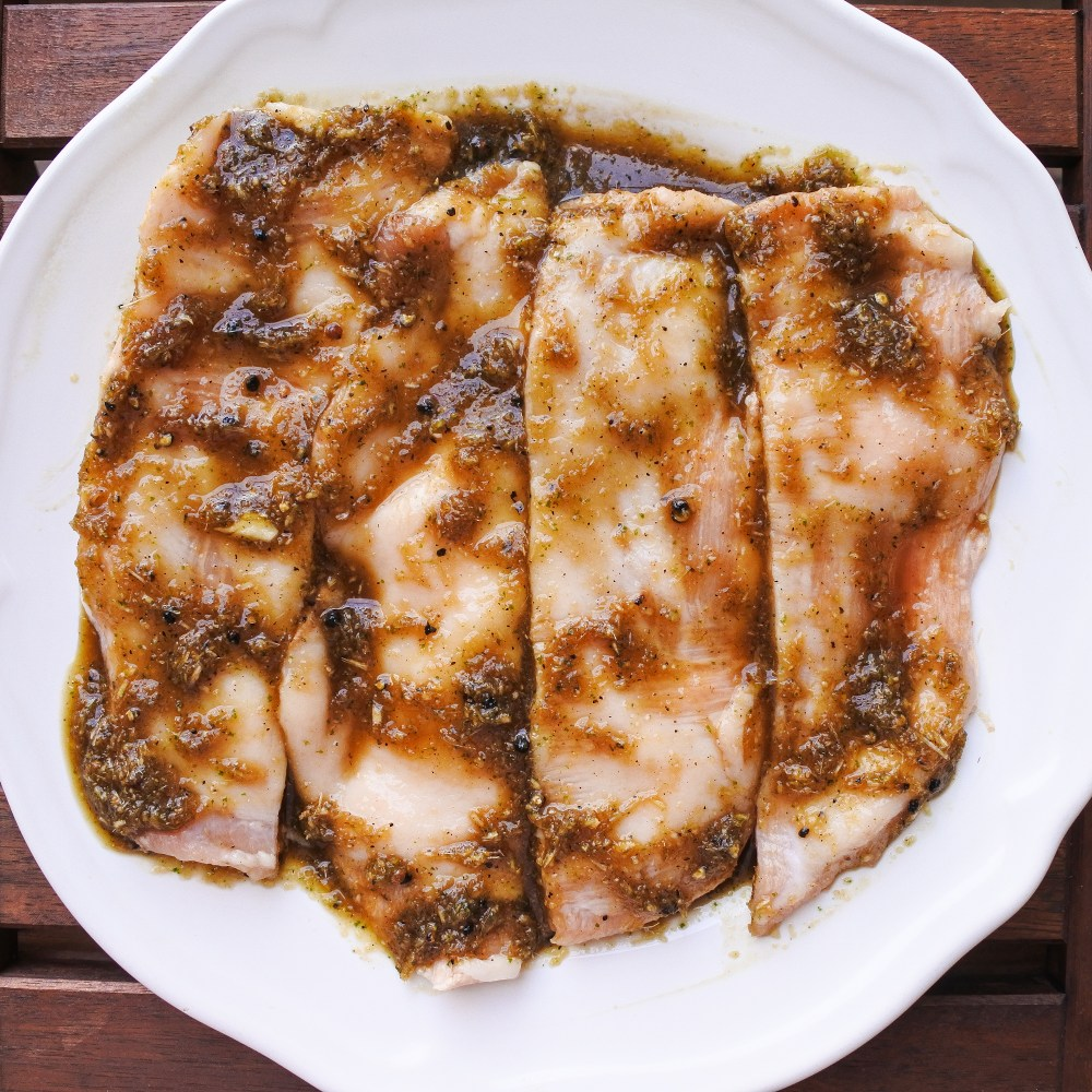 pork jowl marinating on a plate