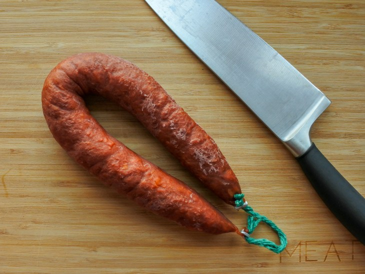 A link of chorizo on a cutting board with a knife.