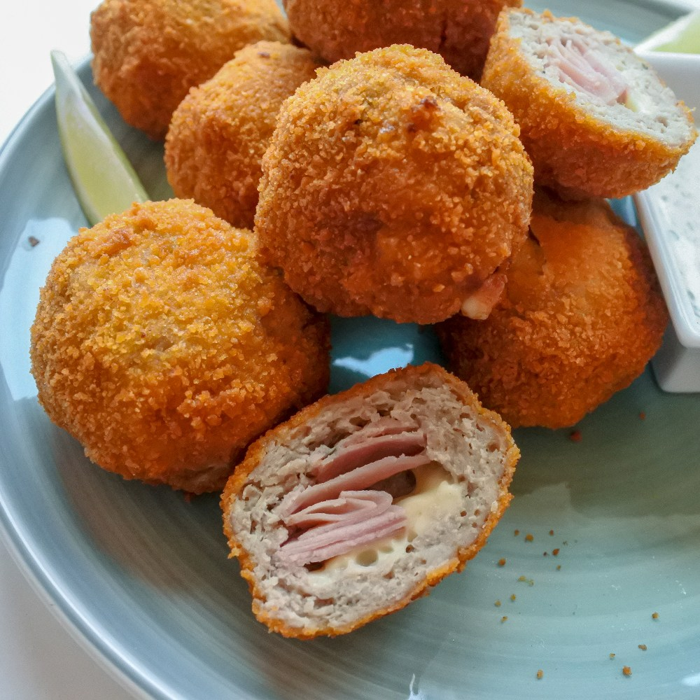 Chicken cordon bleu bites on a plate with a lemon wedge