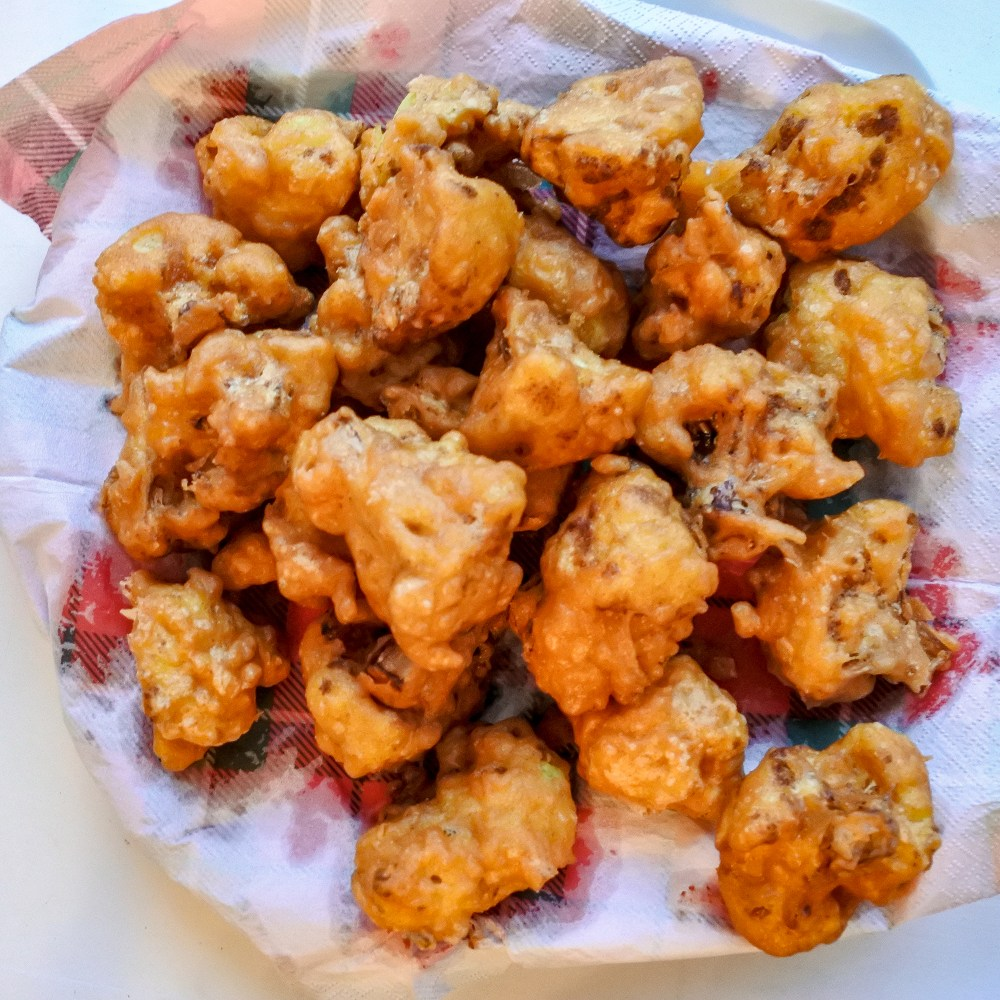 Fried cauliflower florets on a plate lines with paper towls