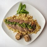 sliced stuffed lamb hearts on a plate with couscous, mushrooms, mint and a green sauce