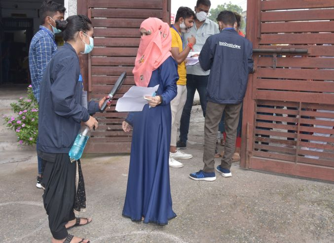 Agency personnel checking the candidate who arrived from SAM Inter College to give PET exam