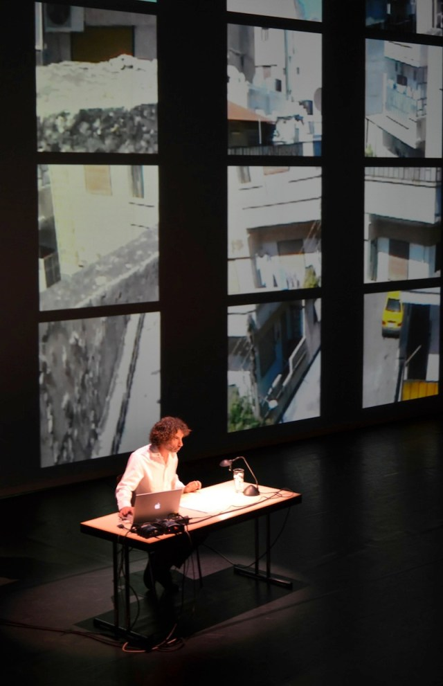 Rabih Mroué sitting at a desk on stage, with several square projections of video behind him.