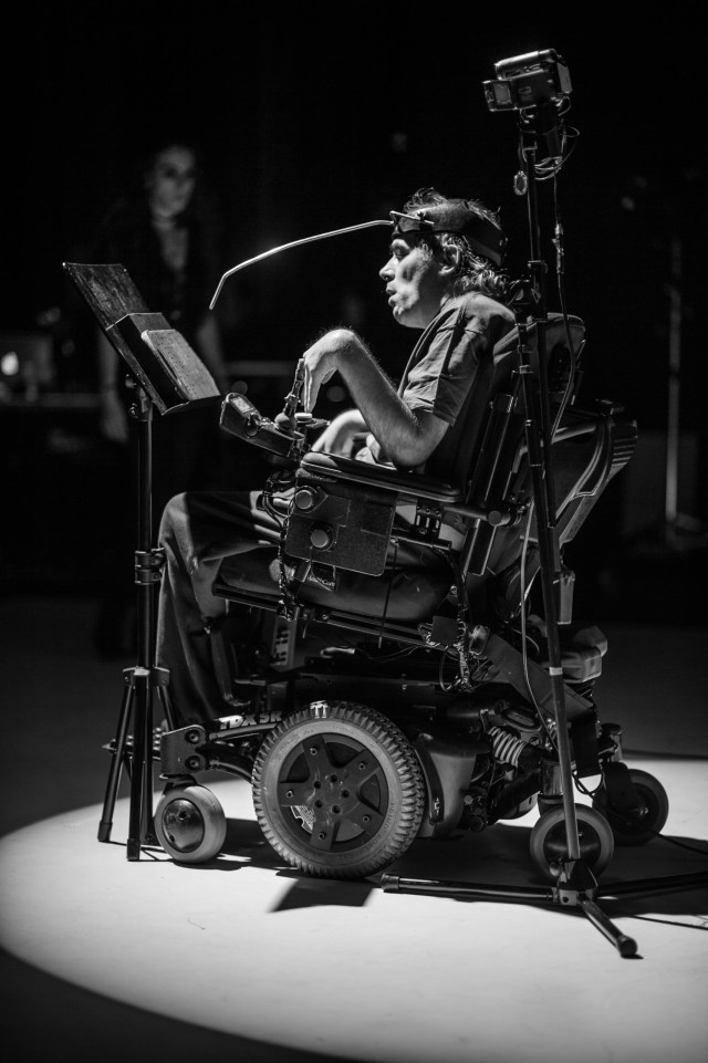 Man in a wheelchair on stage, performing with a live feed camera and letter board.