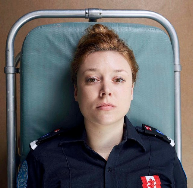 Hovering above the face of a female paramedic laying on a stretcher.