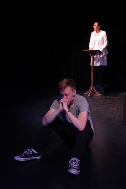 Downstage, Jonathan sits on the ground with his hands folded in prayer in front of his mouth. Upstage, a woman in all white stands at a pulpit.