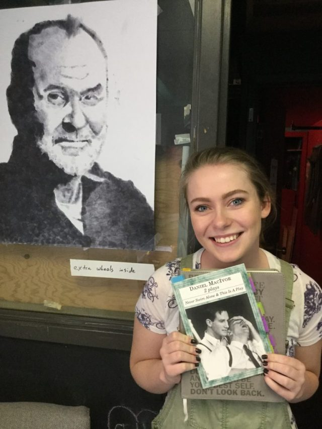 Jane, high school girl, holds a copy of Never Swim Alone by Daniel MacIvor while standing in front of a portrait of the author.