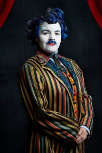A young woman, her face painted white, dressed in a colourfully striped men's suit with blue hair and a blue mustache.