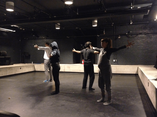 Four actors stand in a cluster in the middle of a blackbox theatre, with their arms extended wide.