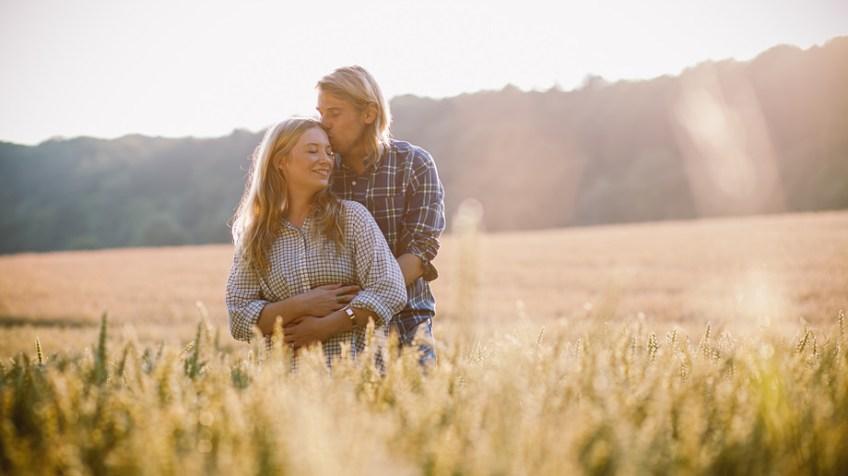 Porträt eines jungen Paars im Getreidefeld beim Sonnenuntergang