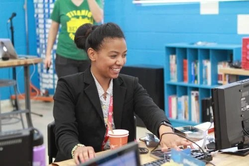 A teacher works at a computer, smiling delightedly. Another adult, standing in the background, observes. national centre for computing education