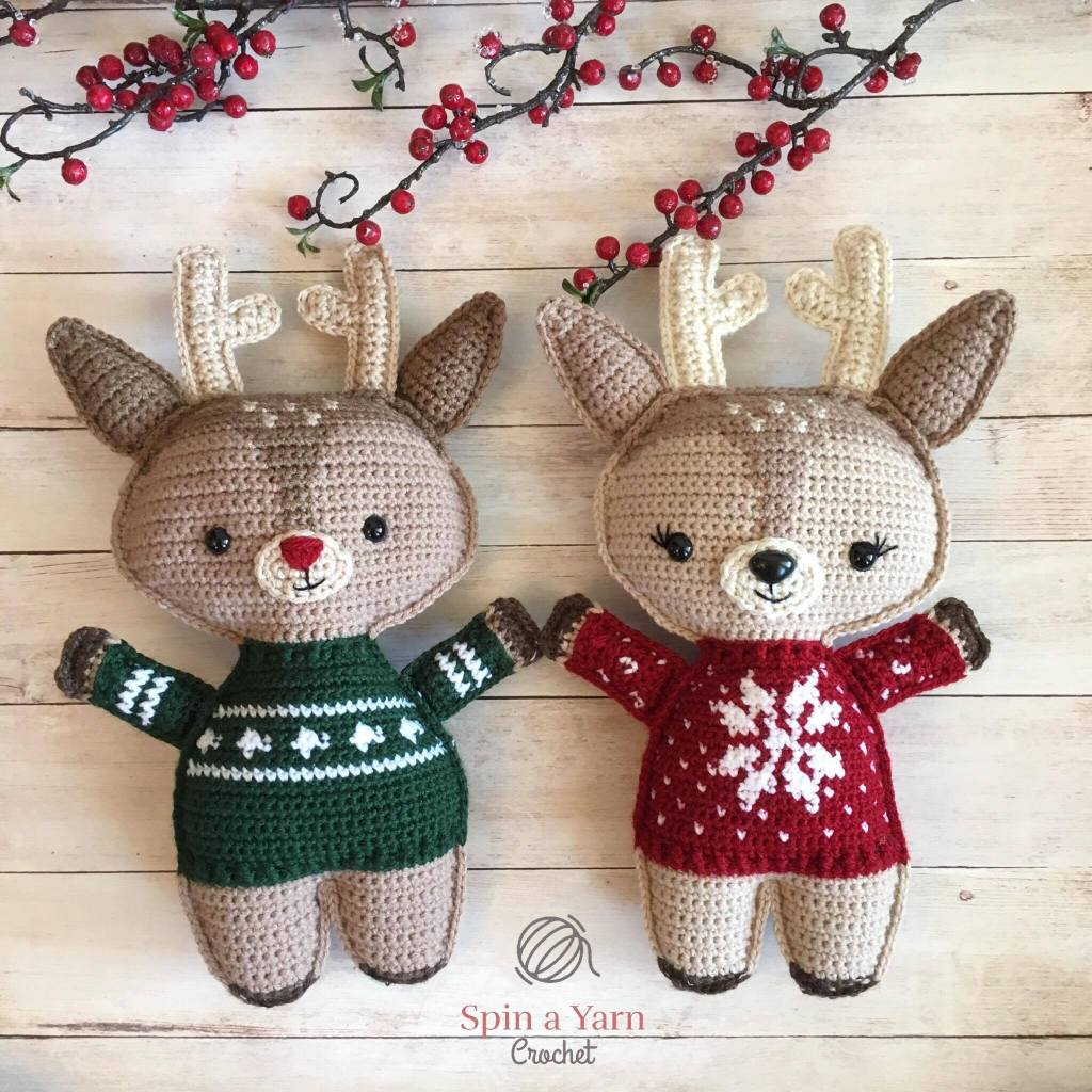 crocheted reindeer, one wearing a red sweater and one in green.