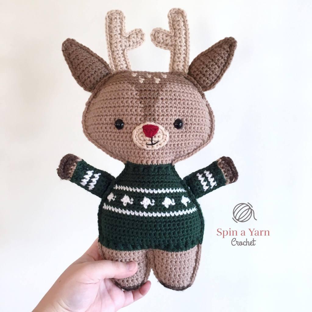 Reindeer wearing green sweater held in air