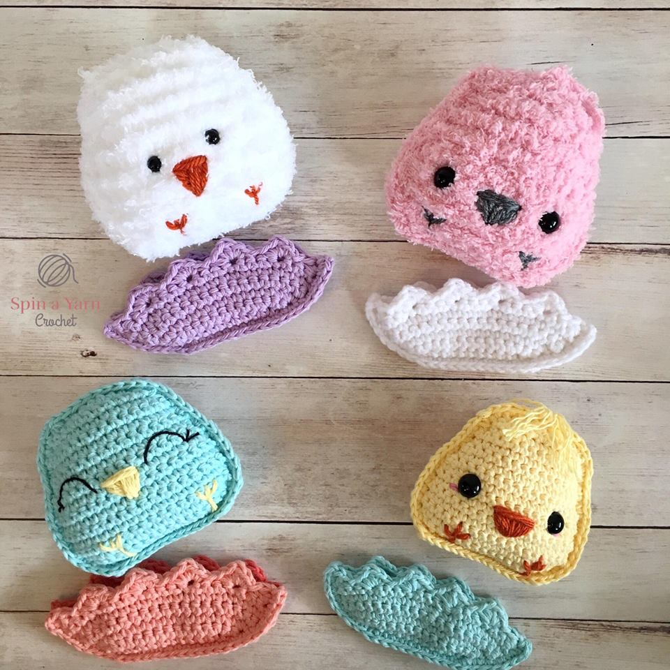Four chubby crochet chicks lying next to eggshells