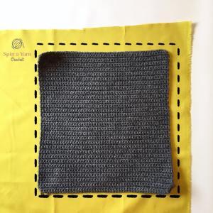 Grey crochet panel lying on fabric
