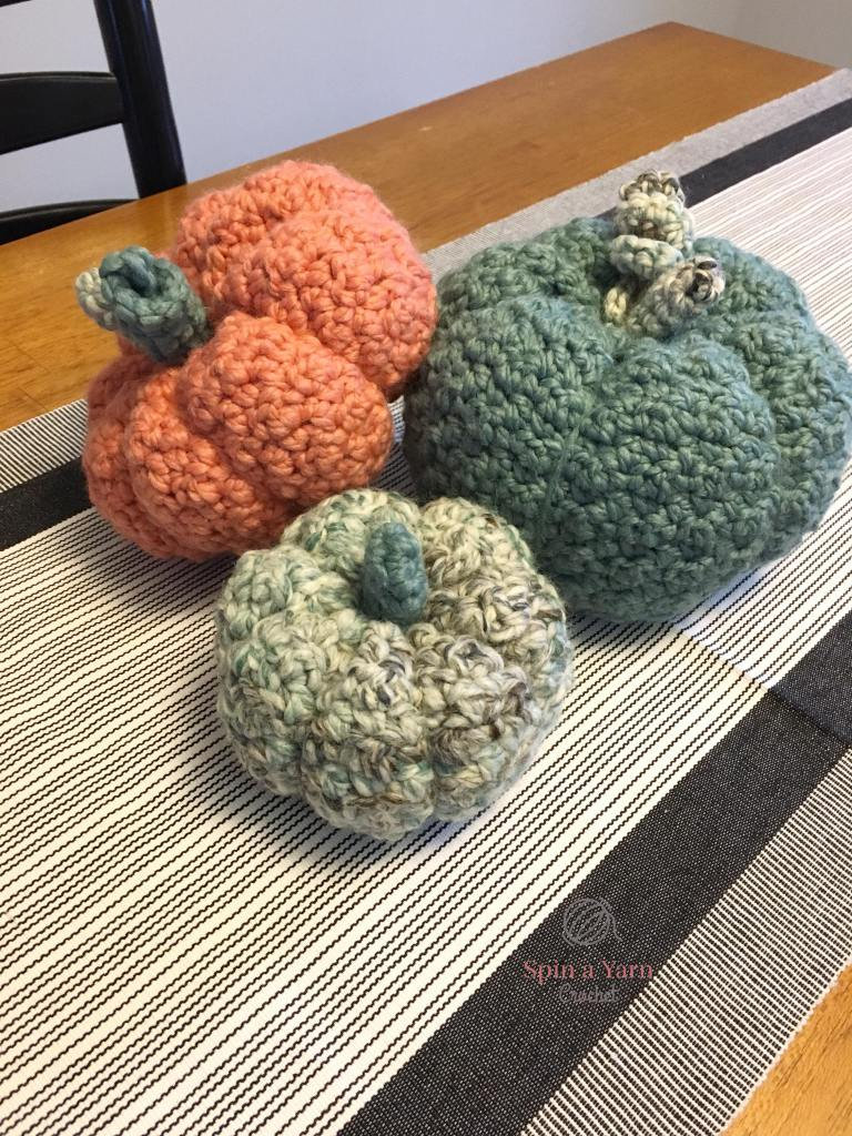 Three crocheted pumpkins on table
