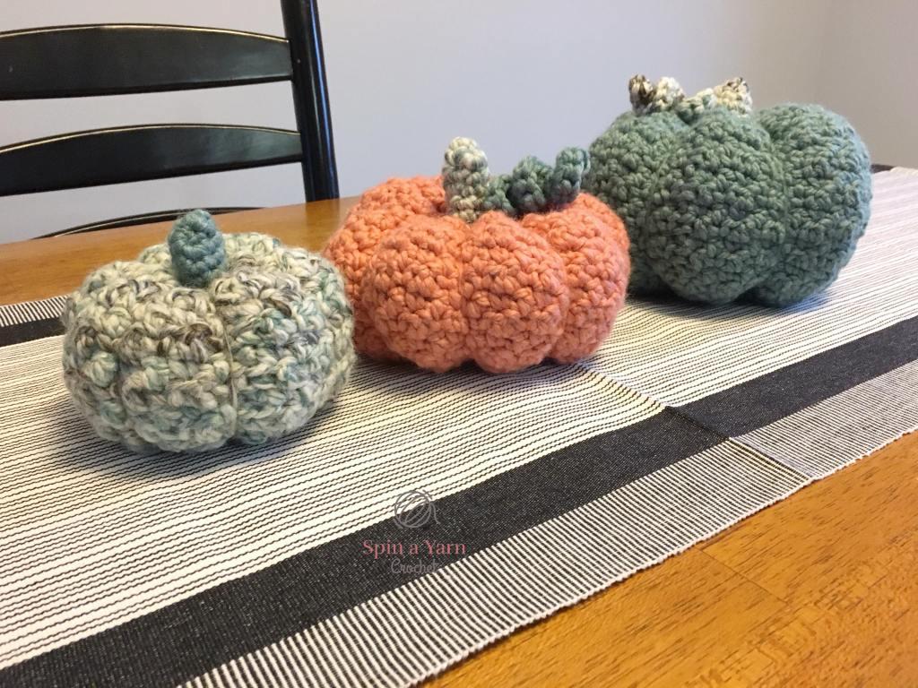 Three crocheted pumpkins on table