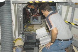 Engineer testing wiring in the Space Shuttle Discovery