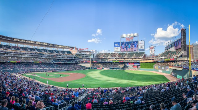 Photo of Target Field in Minneapolis. It is a bright sunny day as shadows cast shapes on the lush green grass of the outfield. Photo Credit:Spintheglobe.net