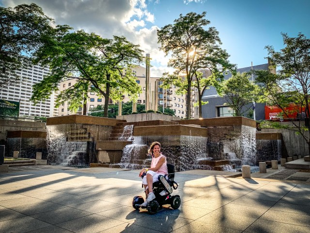 Author of this blog sits in her wheelchair in-front of a stunning stone wall sculpture that features waterfalls running from the top of all the rocks. The Photo is near the Nicollet Mall in Minneapolis. Photo Credit: Spintheglobe.net