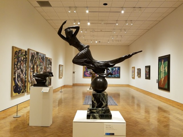 Photo of Gallery inside the Minneapolis Institue of Art features a large dark colored sculpture of a dancer in the center of the room, surrounded by paintings on the outer walls. Photo Credit:Spintheglobe.net
