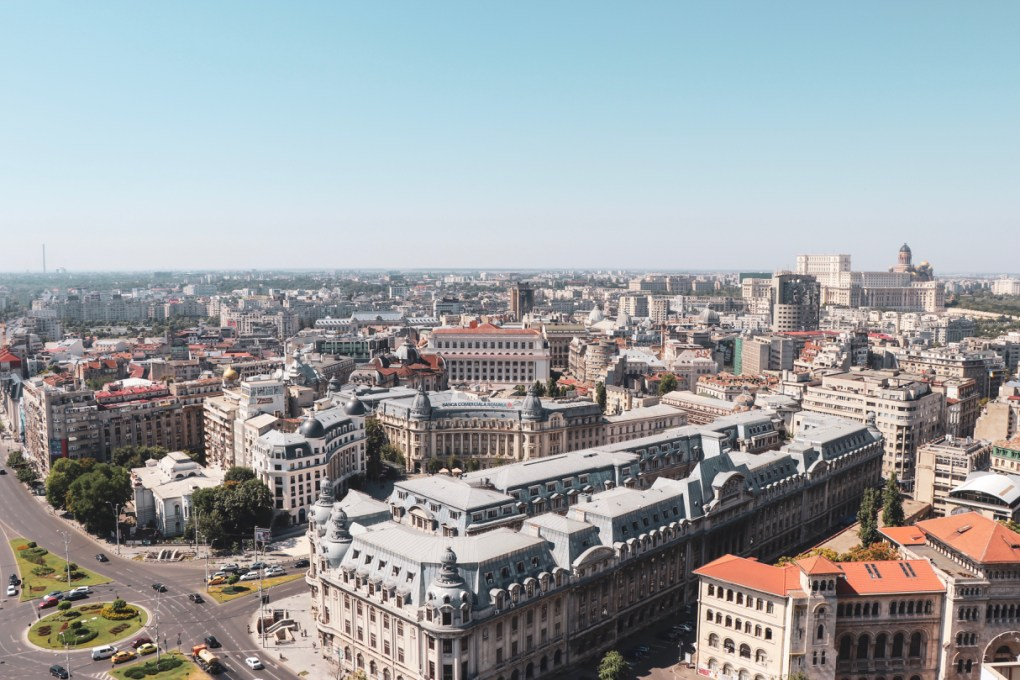 The skyline of Bucharest is stunning, with ornate buildings as well as modern structures. A church sits on the horizon and the sky is clear blue. 11 must-visit photo spots in Bucharest - spinthewindrose.com