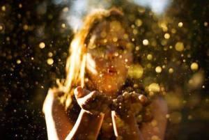 femme qui souffle des paillettes dans ses mains, magie et féérie