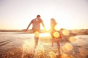 couple main dans la main qui court vers le soleil sur la plage, couple sacré