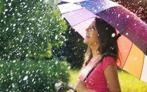 femme souriante avec un parapluie multicolore qui rit à la pluie