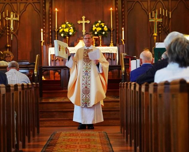 Fr. Ken Chumbley presents a kneeler. Image credit: Franz Ginsberg