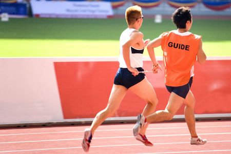 A blind man running a 100 meter race with a guide.