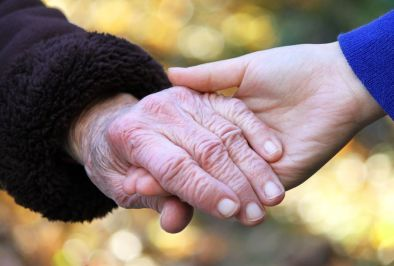 A young person holding a senior's hand without judgment.