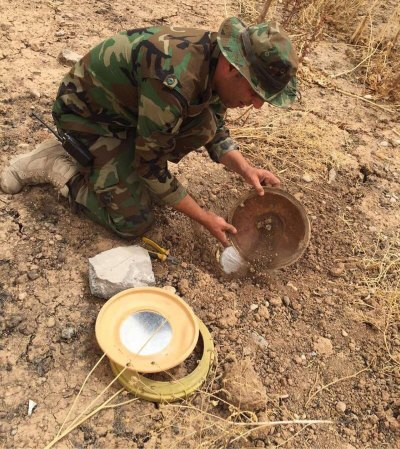 Captain Dilgash, Peshmerga commander, dismantling an ISIS-planted explosive device using tools provided by SoA