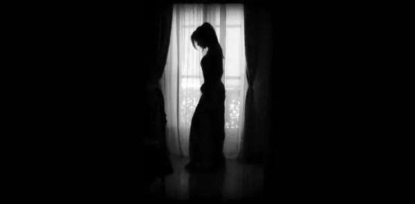 暗い部屋でうなだれる女性