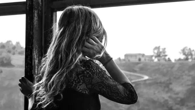 耳を押さえる女性 窓 景色を見る